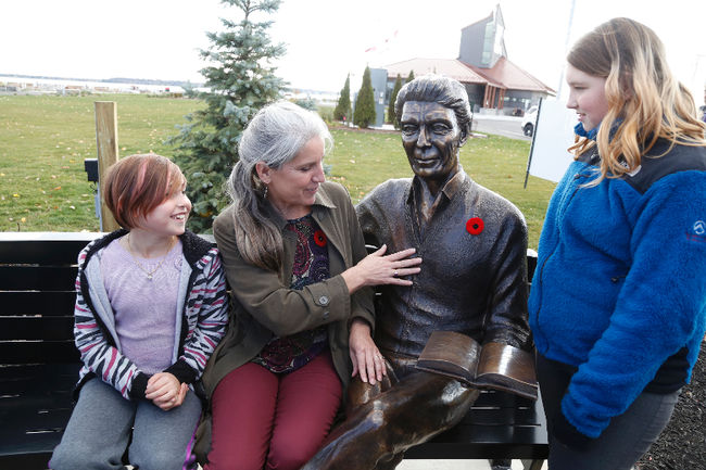 Lesley Bonisteel, muses over the bronze statue of her late father, Roy Bonisteel, with his great-granddaughters, Abbigail Bonisteel-Lajoie, 7, and Melody  Bonisteel-Lajoie, age 10.